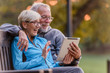canvas print picture - Smiling senior active couple sitting on the bench looking at tablet computer. Using modern technology by elderly.