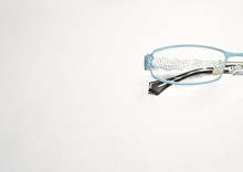 Optics. The Medicine. On A White Background, Women's Glasses With Transparent Lenses In A Blue Openwork Metal Frame.
