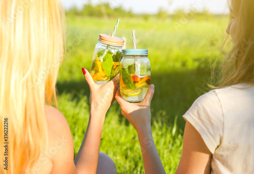 Girls holding fresh lemonade in jars with straws Tableau sur Toile