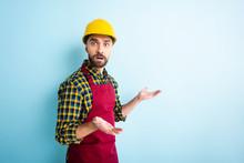 Confused Workman In Safety Helmet Showing Shrug Gesture On Blue