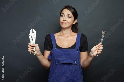 Fotomural ragazza mora vestita con una tuta da meccanico sta con una chiave inglese in man