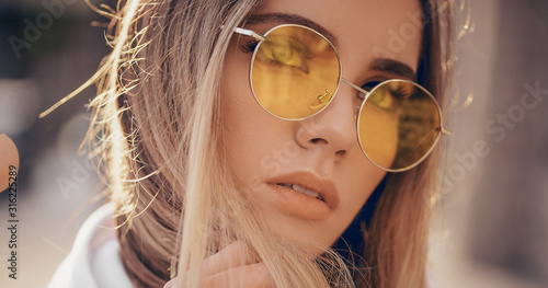 Fotografie, Tablou Portrait of beautiful stylish blonde woman in yellow sunglasses in outdoor