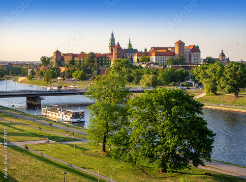 Fototapeta Krakow, Poland, with Wawel castle and cathedral, Vistula river, Podwawelski bridge, a restaurant on the  barge, trees and promenades in summer. Aerial view obraz