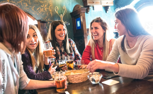 Obraz Happy women drinking beer at brewery restaurant - Female friendship concept with young girlfriends enjoying time together and having genuine fun at cool vintage pub - High iso image with soft focus - fototapety do salonu