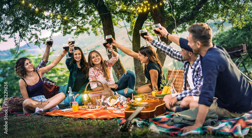 Happy friends having fun at vineyard on sunset - Young people millenial toasting at open air picnic under string light - Youth friendship concept with guys and girls drinking red wine at bar-b-q party - 316229636