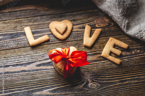 Message from a sweet cookie in the form of the word love and a gift tied with red ribbon. Romantic Valentine's day gift