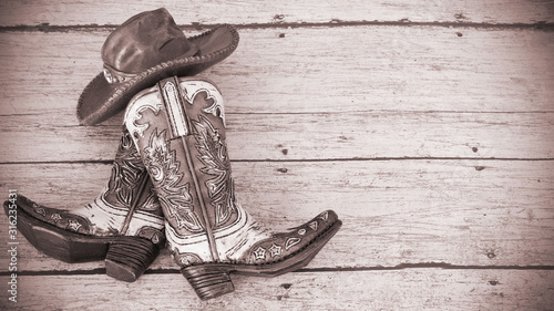 cowboy boots and hat on a wood background with vintage tinted effect and writing Wallpaper Mural