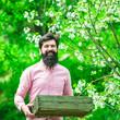 Leinwandbild Motiv Lifestyle and family life. Professional Gardener at Work. Bearded man gardener in an urban garden. Become organic farmer. Happy Farmer hold box.