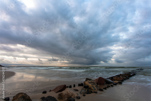 Baltic sea beach with stones and old breakwaters under a gloomy cloudy sky at lo Tableau sur Toile