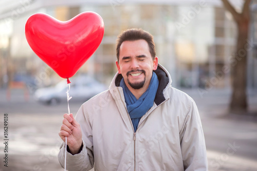 Photo Portrait of smiling man standing with closed eyes and holding with  red air balloon shaped like heart