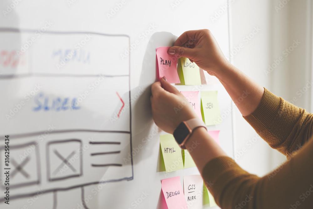 Fototapeta Female web designer planning website ux app development on whiteboard