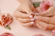 Close up of woman's hand holding elegant diamond ring.