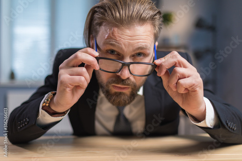 Close-up of bearded businessman adjusting glasses and carefully looking over the Canvas Print