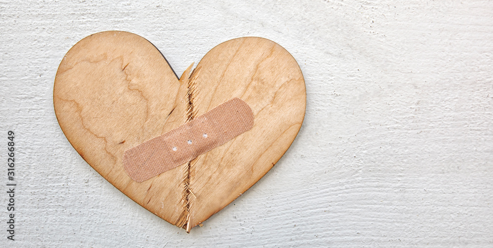 Fototapeta Two parts of broken wooden heart taped by a patch. Concept of the forgiveness, renewal of relations and healing