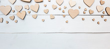 A Beautiful Background With  Lot Of Wooden Hearts On The White Table