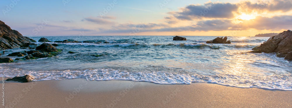 Fototapeta sunrise on the beach. beautiful summer scenery. rocks on the sand. calm waves on the water. clouds on the sky. wide panoramic view