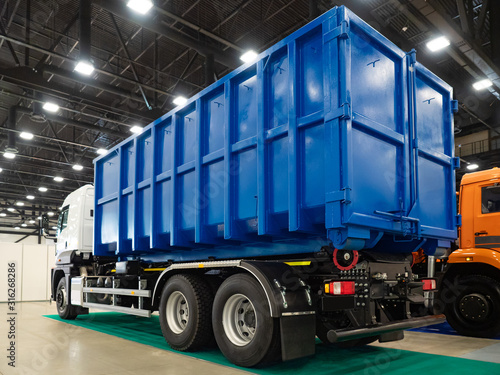 Fototapeta Demonstration trucks. Blue truck body. The body of the truck for garbage collection. Demonstration of equipment for housing and communal services. Metal container for garbage collection on wheels. obraz