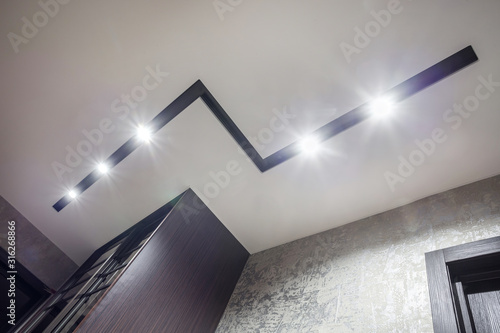 Obraz halogen spots lamps on suspended ceiling and drywall construction in in empty room in apartment or house. Stretch ceiling white and complex shape. - fototapety do salonu
