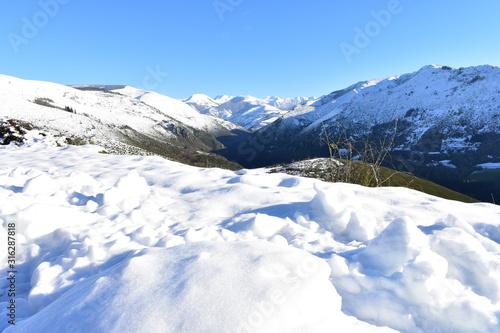 Winter landscape with snowy mountains and green valley. View from a peak with ice, snow and blue sky. Ancares Region, Lugo Province, Galicia, Spain.
