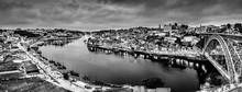 Black And White Night Cityscape Panorama Skyline Of Porto Old Town, Luis I Bridge And River Douro Banks With Reflections.