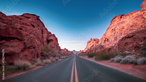 Fototapeta A road through mountain valley at sunrise. Valley of Fire, Nevada