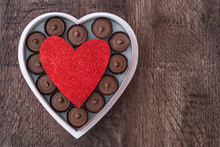 Simple Heart Shaped Box Of Chocolate Peanut Butter Cup Valentine's Day Candy On A Wood Table, With A Red Glitter Heart