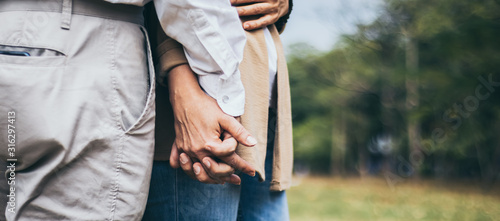 Obraz Lovely senior elderly smiling couple man and woman holding hand as promising of forever love or take care in romantic moment. Warm heart marriage and lover bonding and relationship. Love photo concept - fototapety do salonu