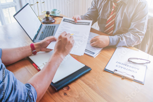 The lawyer is giving legal advice to investors and discussing legal contract documents to be used as a contract between investors signing a consent to invest in doing business together Canvas Print