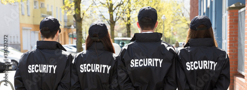 Fotografia Rear View Of Security Guards Standing In A Row