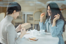 Two Young Women In Cafe Giving...