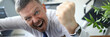 Leinwanddruck Bild - Crazy boss screams threatens with a fist and looks at camera against business office background.