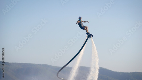 Fotografía  extreme athlete is using flyboard on sea, moving legs and torso to control movem