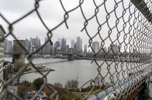 Fence Hole On Manhattan Bridge With Downtown Manhattan And Brooklyn Bridge On The Background