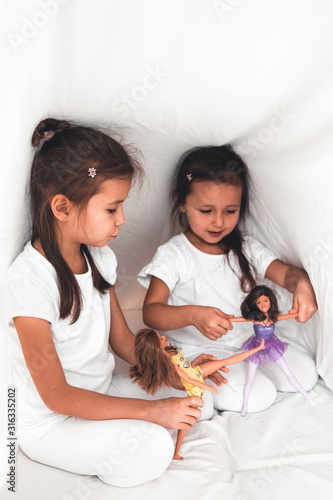 Little girls in bed play with dolls. Joy, family, fun Canvas Print