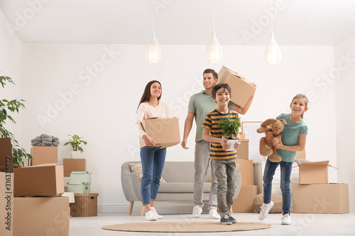 Fototapeta Happy family in room with cardboard boxes on moving day obraz