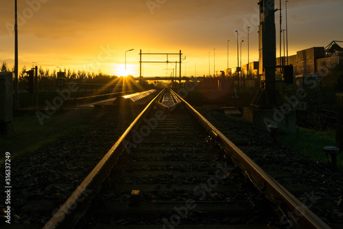 Fototapeta Railroad track vanishing in the distance at sunrise