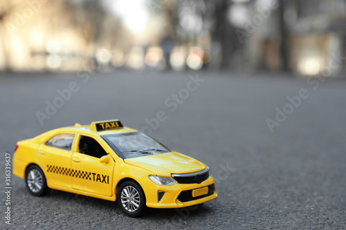 Fototapeta Yellow taxi car model on city street. Space for text