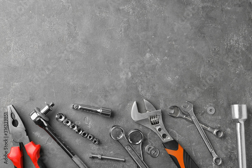 Fotografía Auto mechanic's tools on grey stone table, flat lay