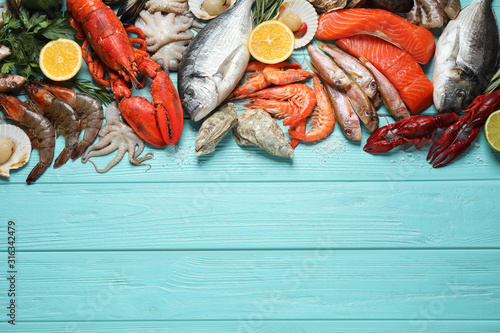 Foto Fresh fish and different seafood on blue wooden table, flat lay
