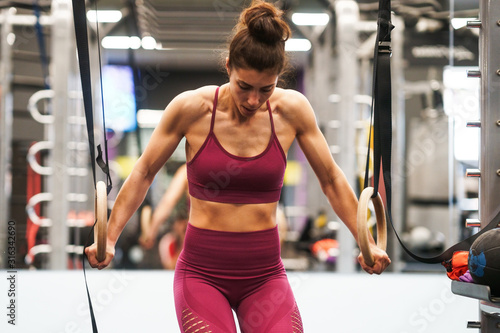 Tela Athletic woman doing some pull up exercises in the gymnastic rings