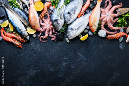 Fototapeta Fresh fish and seafood assortment on black slate background. Top view. Copy space. obraz