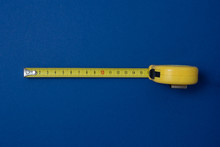 Yellow Measuring Tape On A Blue Background. View From Above.