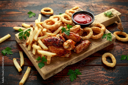 Slika na platnu Fried Chicken wings with onion rings, french fries and dipping sauce