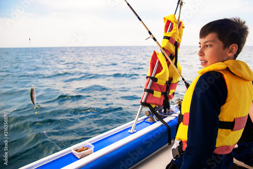 little boy caught fish spinning from a boat at sea Tapéta, Fotótapéta