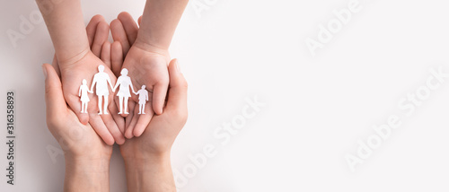 Obraz Family care concept. Hands with paper silhouette on table. - fototapety do salonu