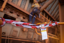 Safety Prevention Red And White Danger Tape And Tag Are Barriers On Exclusion Dropped Object Zone While Defocused Construction Abseiler Working In Fall Arrest, Fall Restraint At The Background