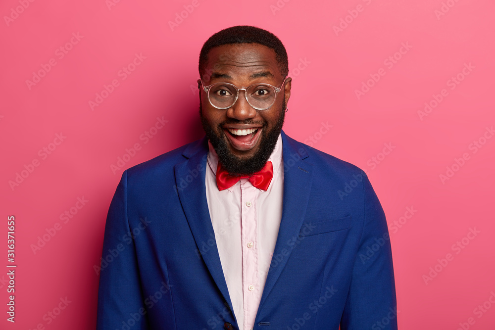 Fototapeta Headshot of glad dark skinned man looks positively at camera, being in high spirit, talks casually with colleagues, wears formal clothes, models against pink background., has happy reaction.