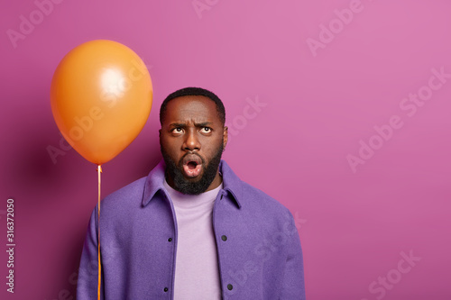 Surprised man frowns face, looks above with displeased shocked expression, thinks about something unpleasant, wears purple clothes, holds balloon, poses against lilac background, blank space Wallpaper Mural
