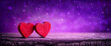 Two Wooden Hearts On Rustic Table With Sparkling Purple Background - Valentine's Day Concept