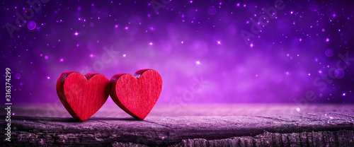 Obraz Two Wooden Hearts On Rustic Table With Sparkling Purple Background - Valentine's Day Concept - fototapety do salonu